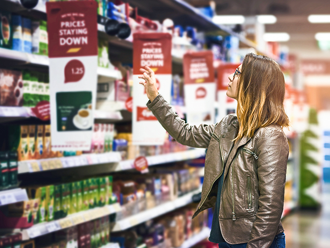 Woman in retail store with shelf talkers and hanging retail signage