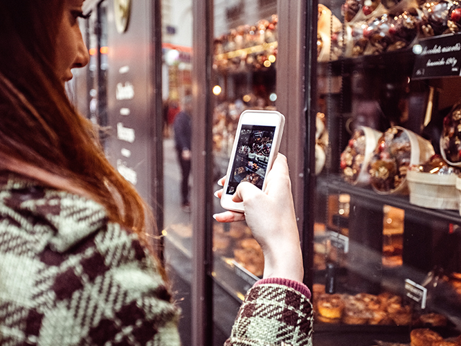 Woman with smart phone looking at retail window display and shelf talker signage