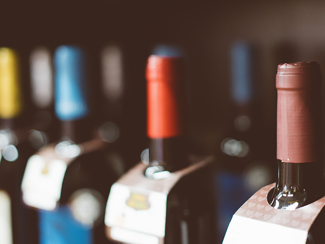 Wine bottles on retail shelf with shrink sleeve caps prime labels and bottle necker hang tags