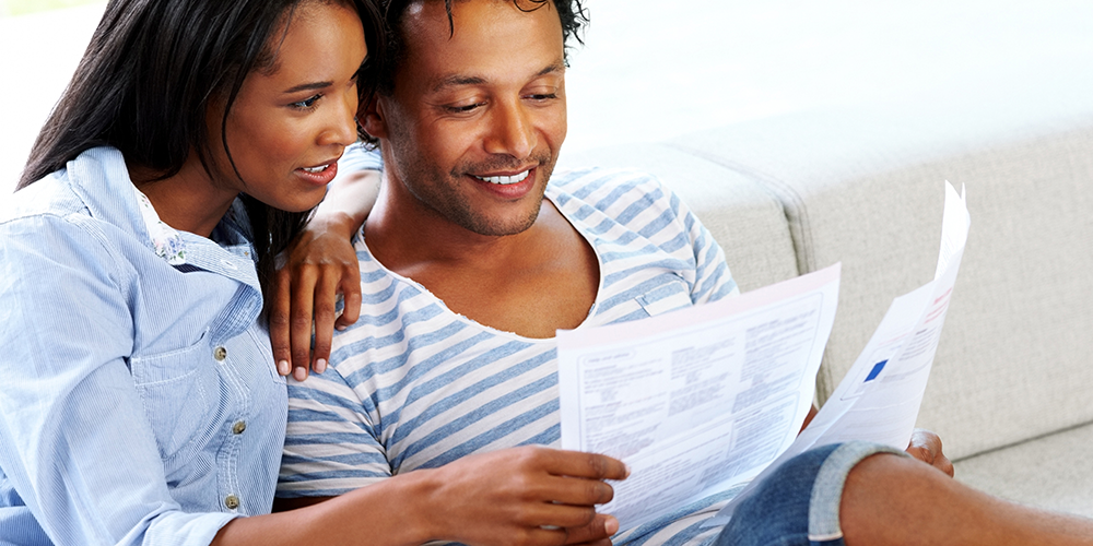 Young couple reviewing printed bank statement received in the mail
