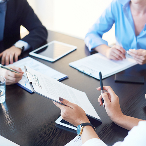 Marketing communications professionals reviewing purchasing contract