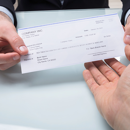 Marketing communications professional holding printed check