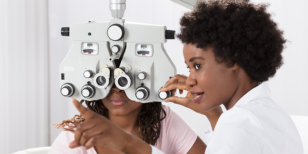 Doctor giving eye exam in eye care clinic