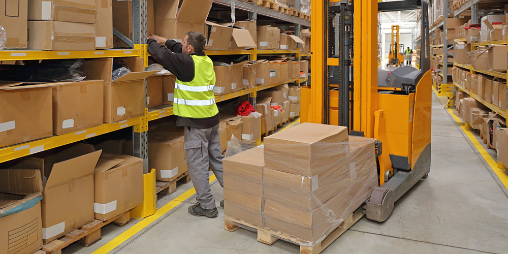 Man working on kitting process in a warehouse and fulfillment distribution center