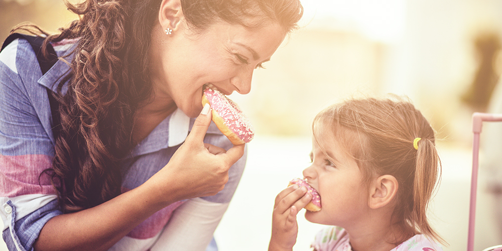Woman and child eating donuts purchased through a gift and loyalty club program