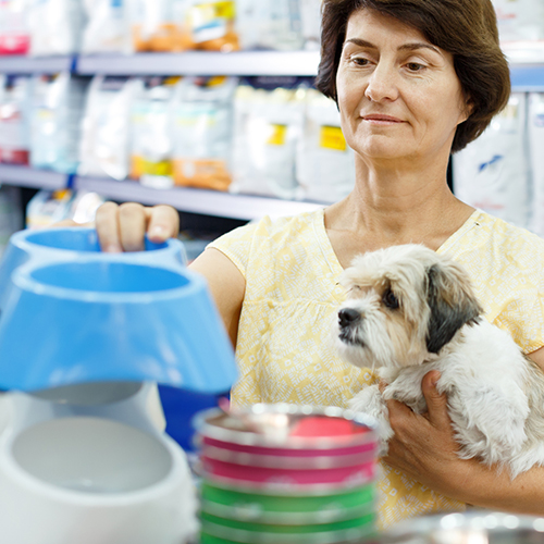 Woman in pet supply store with custom packaging and shelf talker signage in background