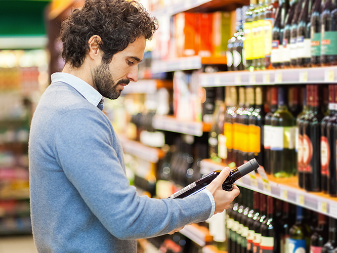 Man reading custom printed prime label on wine label in retail store