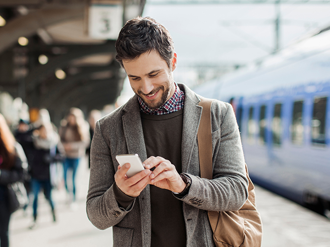 Man in train station interacting with secure customer communication on mobile phone