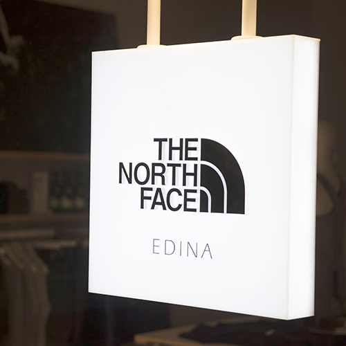 A custom hanging light box sign in a retail store environment
