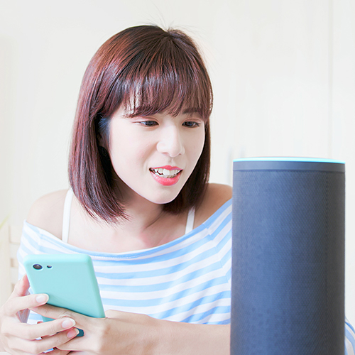 Woman using voice activated virual assistant and mobile phone to make retail purchase