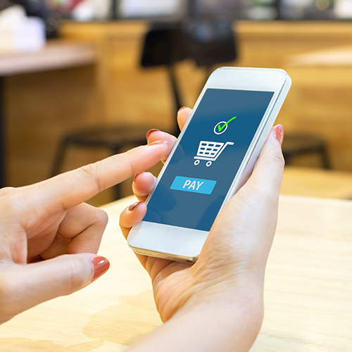 Woman using mobile phone payment app to make retail purchase