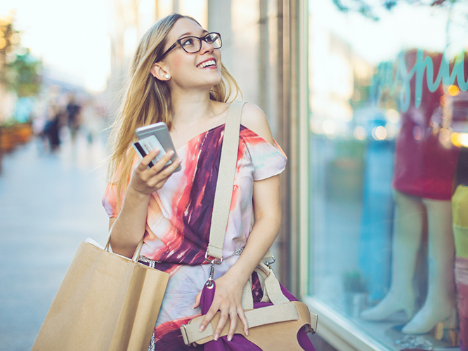 Millennial woman using smartphone at retail store with window signage and other visual merchandising in background
