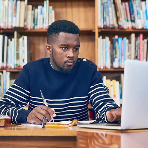 College student in a library using a laptop computer to study and complete coursework