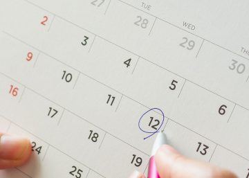 Woman circling date on marketing event calendar as opportunity for promotional marketing products