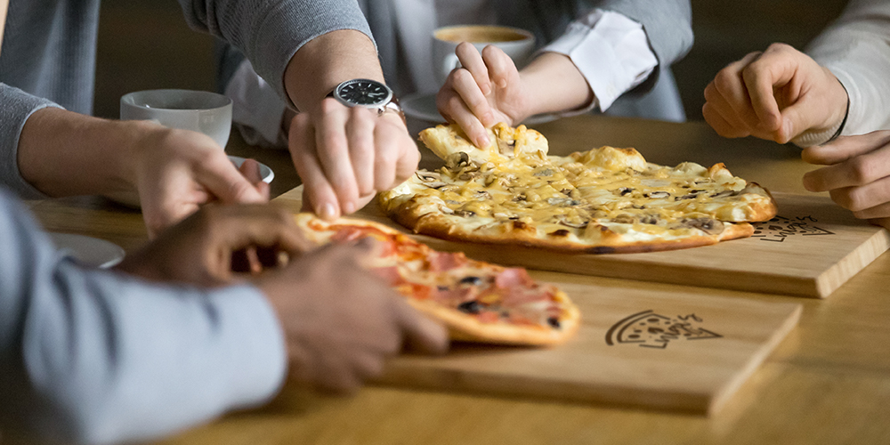 Friends eating pizza from custom-imprinted serving boards in a retail restaurant setting
