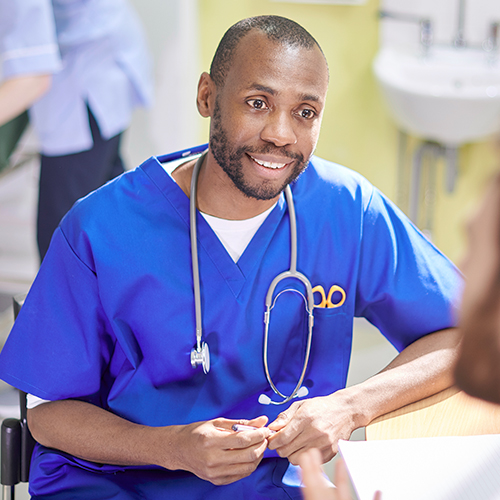 Nurse with printed documents communicating with a patient in a corporate healthcare setting