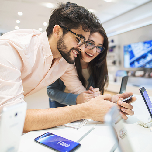 Customers in a retail setting having a positive customer experience with a mobile phone device