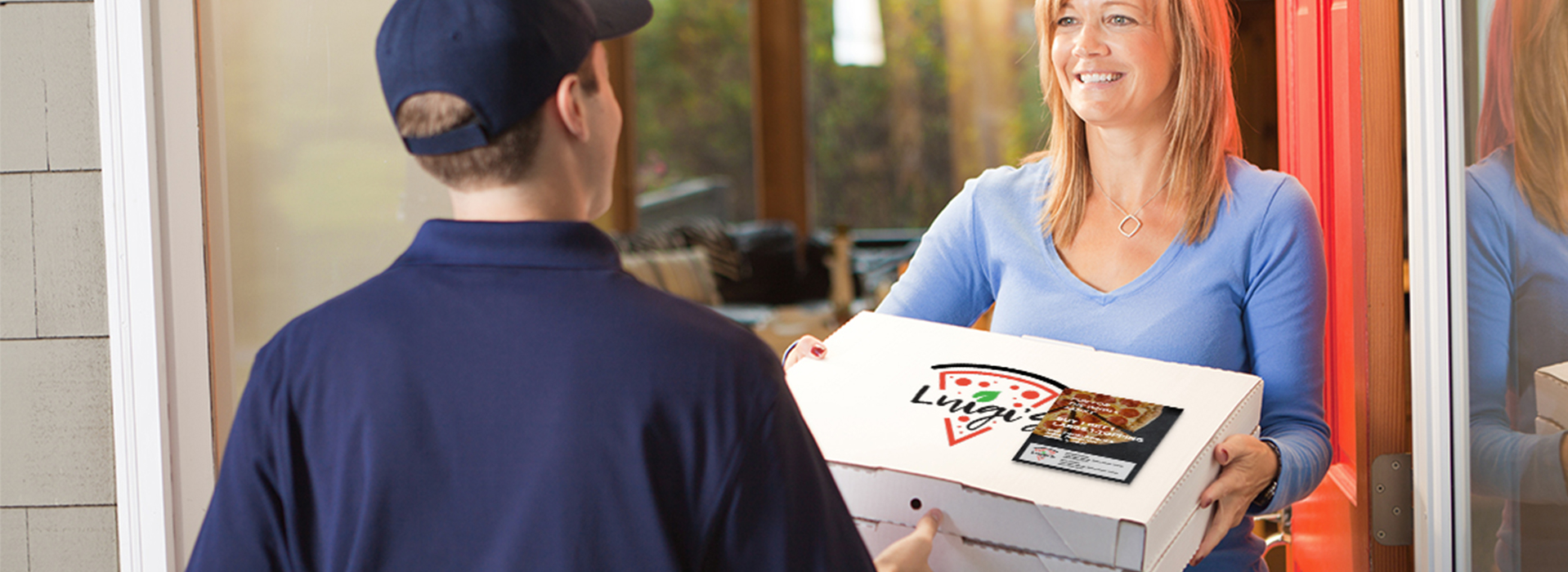 Pizza delivery driver wearing logo-branded apparel delivering pizza with custom-printed Post-it Note coupon on box top