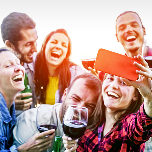 Millennial consumers with wine glasses and wine bottles taking photograph