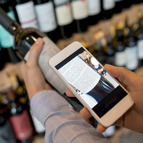Millennial consumer using a mobile phone augmented reality app to evaluate a wine bottle label
