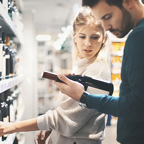 Millennial consumers shopping for wine reading wine bottle labels and store signage