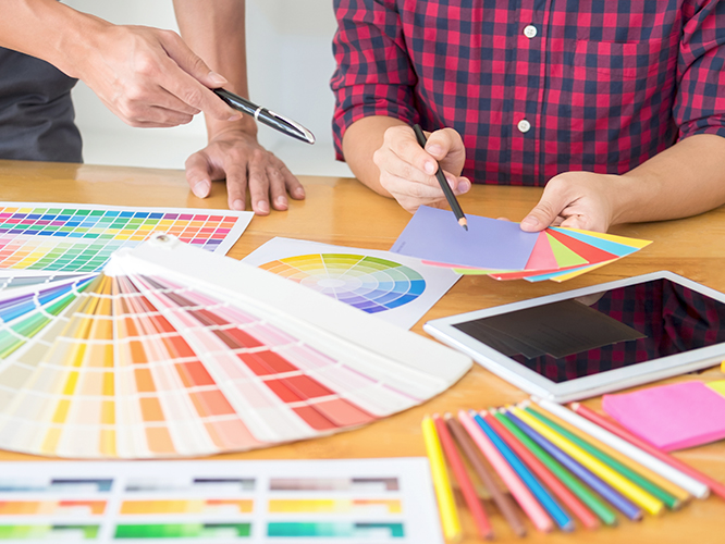 Marketing communications professionals reviewing Pantone color options for high-end print project