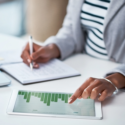 Marketing communications manager reviewing data analytics report on a tablet digital mobile device