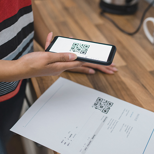 Marketing communications manager using smart phone to scan a QR code on a printed invoice statement