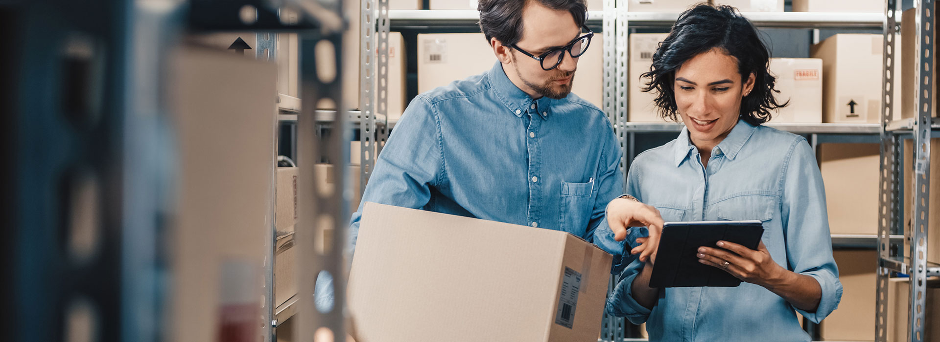 Warehousing and distribution employees in a warehouse setting check the status of a package delivery
