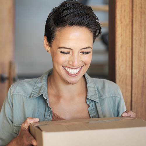Woman receives a folded carton package delivery at home