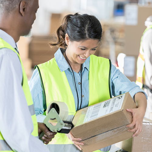 Warehousing and fulfillment employees handling packages with direct thermal-printed shipping labels