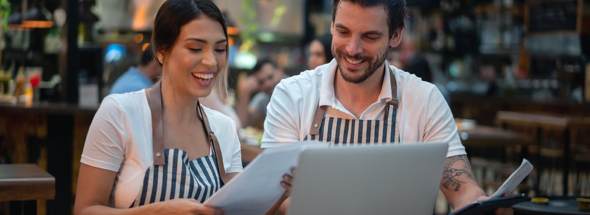 Restaurant employee training coworker on computer