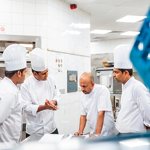 Restaurant employees reviewing menu in kitchen