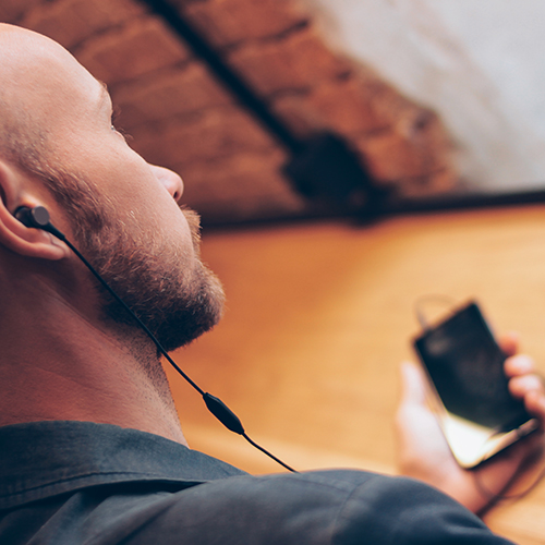Man in coffee shop listening to podcast on smart phone