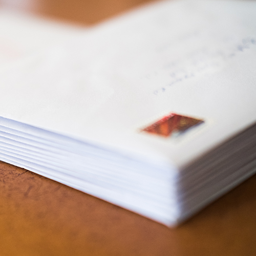 Stack of stamped letters to mail to prospects and clients