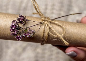 Woman giving custom wrapped gift with flowers for the holidays