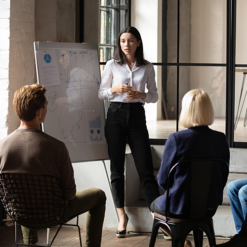Woman presenting marketing strategy on whiteboard to team