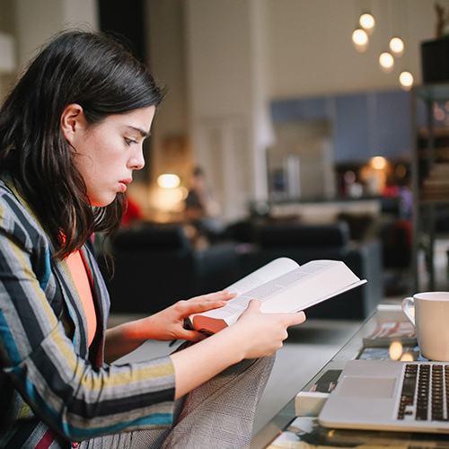 woman-reading-book-at-desk