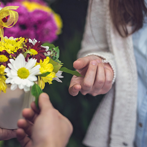 Woman receiving surprise flower delivery from delivery man