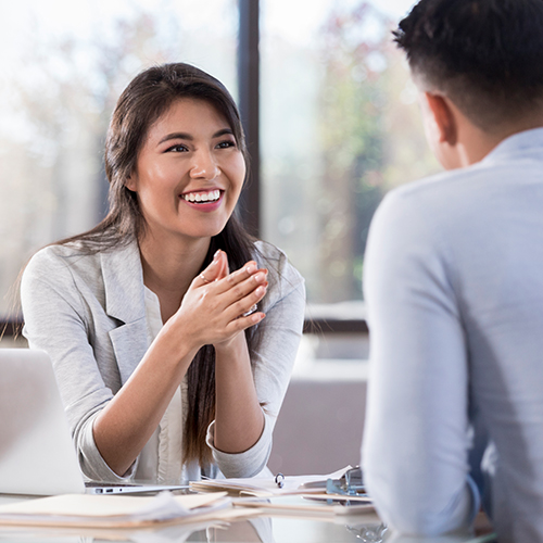 Woman sitting at her desktop sharing information with male client