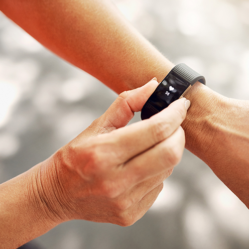Woman using fitness tracker device on wrist while exercising outside