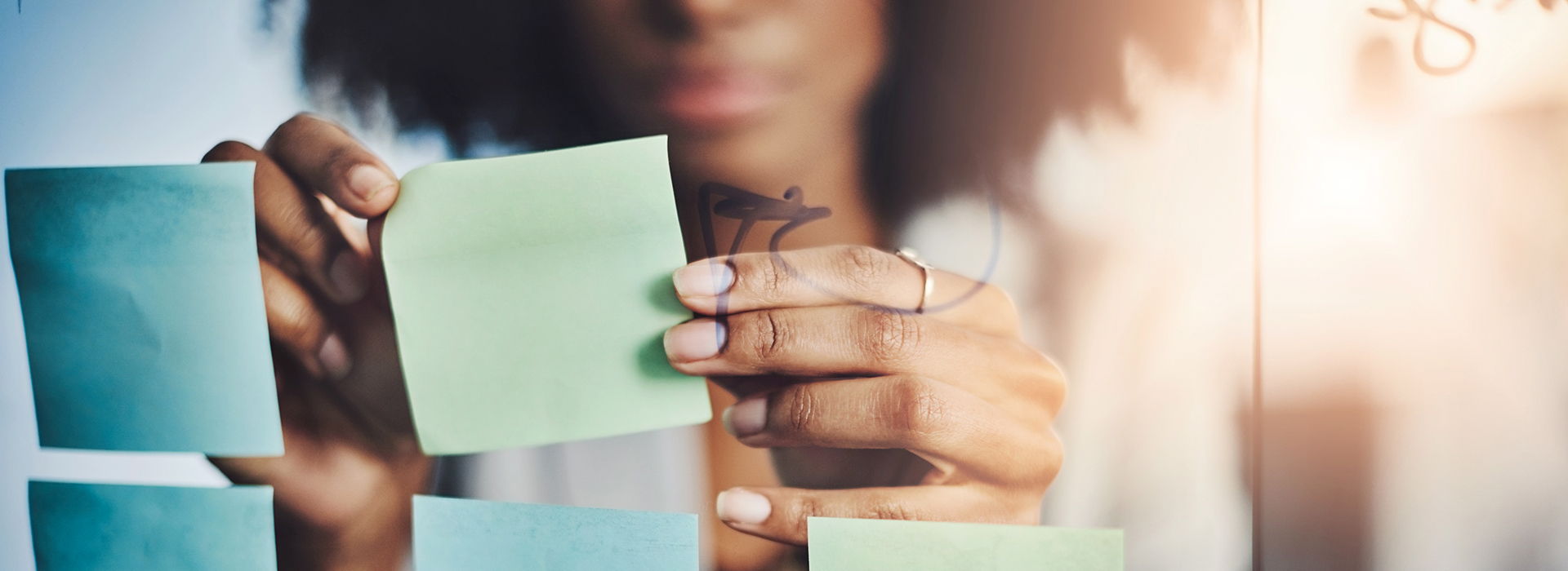 Woman in office using sticky notes on board for project planning